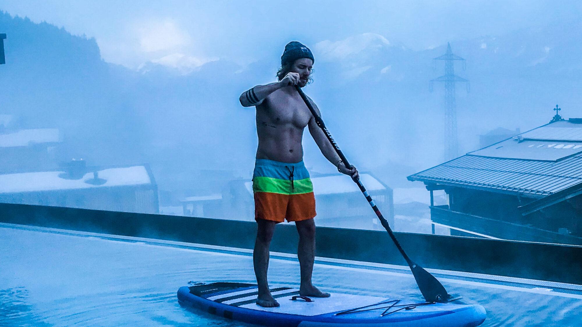 Paddeln aufm Dach: Früh morgens beim Stand Up Paddeln auf dem Infinity Pool eines Hotels in Tirol (Österreich).