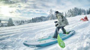Wer braucht schon Wasser? Fürs SUP-Snowboarding braucht's nur einen Hügel, Schnee und ein bisserl Mut.